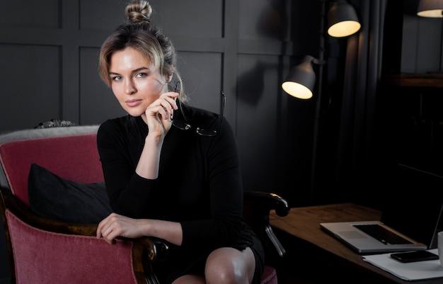Корпоративная молодая женщина позирует в офисе