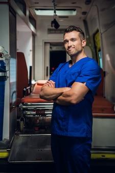 笑みを浮かべて救急車に座っている青い制服を着た軍人