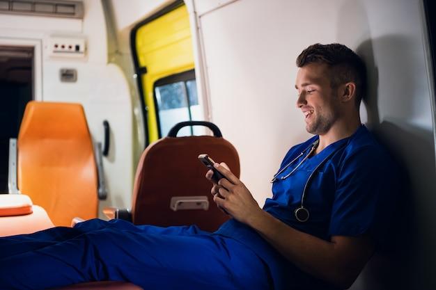 スマートフォンを使用して救急車に座っている青い制服を着た軍人
