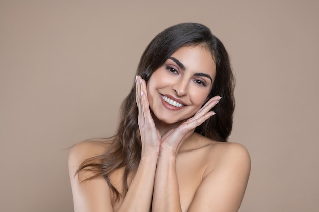 Correct features. happy young dark-haired woman with bare shoulders touching palms to her face on light background