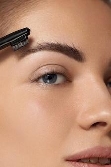 眉の矯正と輪郭付け。くしで眉を形作る美しい女性。眉毛とまつげをクローズアップ