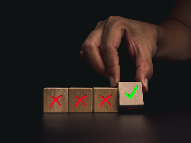 Correction and development concept. close-up hand flipping wooden cube blocks for change from the red cross to the green checkmark on dark background.