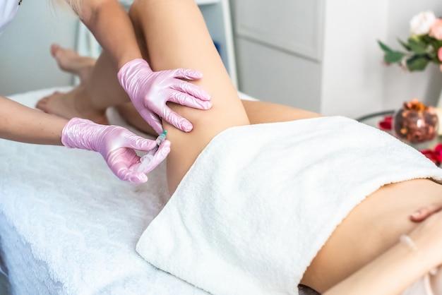 Коррекция жировых отложений липолитиками. в кабинете косметолога женские руки в розовых перчатках колют молодой женщине в бедро.