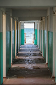 Corridor with doors in an abandoned building during the day and sea view.
