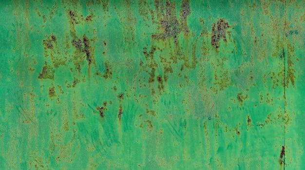 錆の筋を伴う鉄の腐食。細かくひび割れた質感のグリーペイント