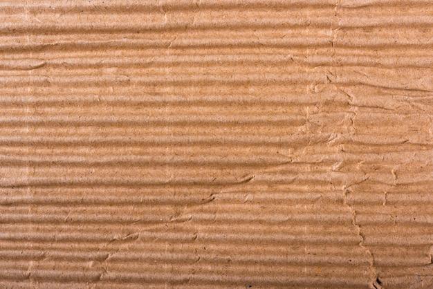 Гофрированный коричневый картонный лист текстуры бумаги или плоской планировки фона