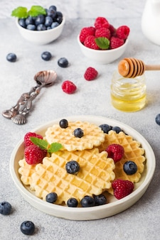 Corrugated waffle cookies with fresh raspberries and blueberries on a concrete background. copy space.