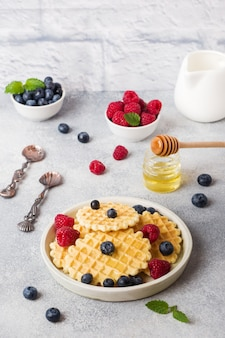Corrugated waffle cookies with fresh raspberries and blueberries