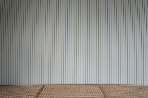 Corrugated wood sheet facade in white color with empty top rattan bench
