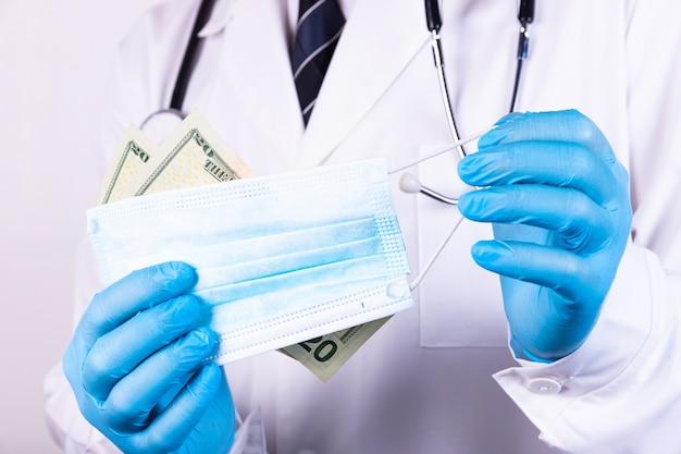 聴診器とネクタイを持った堕落した医者がお金を持っている