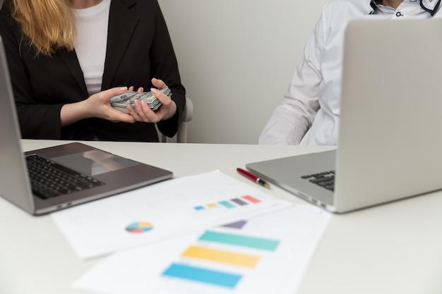腐敗の概念。女性はオフィスに座っている男性にお金を与えます。