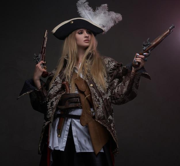 총과 트라이콘이 있는 금발의 해적은 어두운 배경을 바라보고 있습니다.
