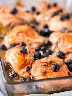 Корсиканские куриные бедра с розмарином, маслинами, чесноком в лимонном соке и вине. куриные ножки, приготовленные в духовке на сером фоне бетона. запеченная куриная ножка в жаростойком стакане. копировать пространство