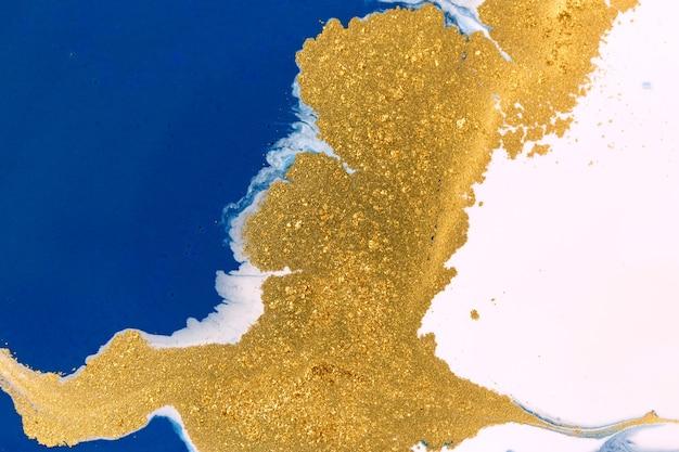 リキッドブルーとホワイトのペイントの背景にゴールドのキラキラを作ります。