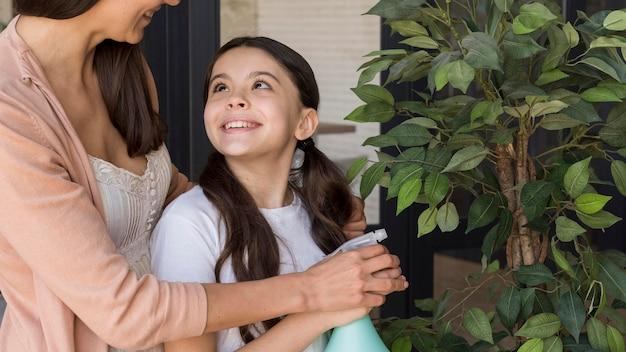 ママと女の子の植物に水をまく