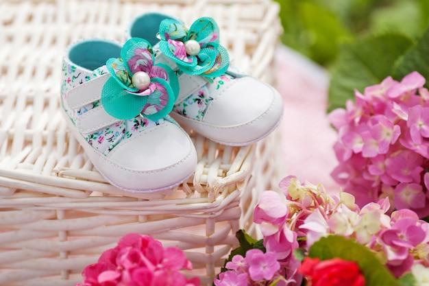여자 아기 신발의 cose-up. 꽃과 함께 야외