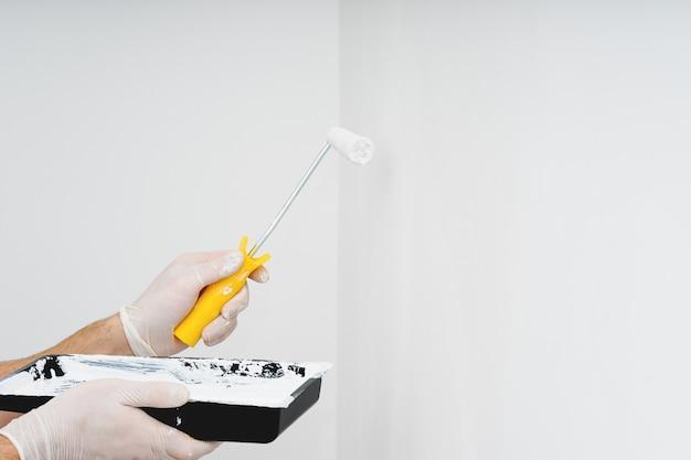 きれいな壁に白いペンキを片手にcoseupペイントローラー