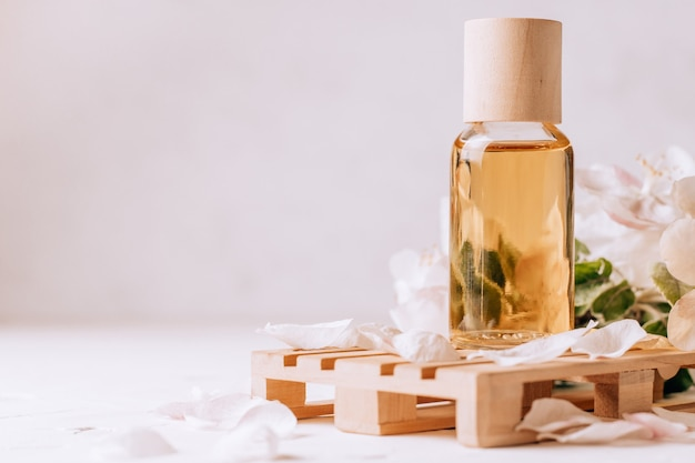 Косметическое, ароматическое или массажное масло на деревянном подиуме в виде поддона на светлой штукатурке с цветами яблони. копировать пространство
