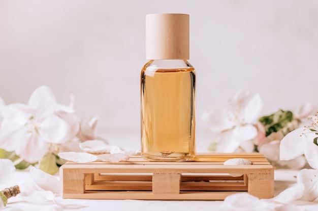 Косметическое, ароматическое или массажное масло на деревянном подиуме в виде поддона, на светлой штукатурке с цветами яблони.