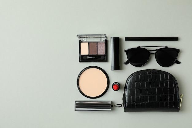 화장품 가방, 메이크업 화장품 및 회색 배경에 sunglasse