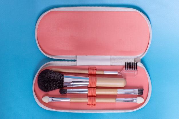 파란색 배경에 화장품 액세서리가 있는 화장품 가방, 여행 키트, 평평한 평지, 복사 공간