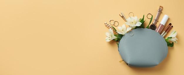 Косметичка с косметикой, украшениями и альстромерией на бежевом фоне