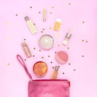 Cosmetic bag with makeup products, cream jars, gel bottles, silicone facial cleansing brush, hydrogel eye patch on pink  with golden stars