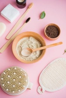 Cosmetic bath salt, grape gomaj for the face, coffee scrub for the body on a pink surface