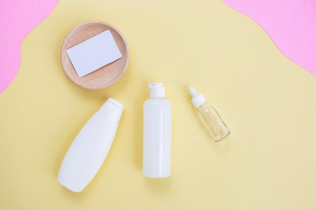 Косметическая бутылка красоты фон и визитная карточка на желтом и розовом бумажном фоне. концепция ухода за кожей летом