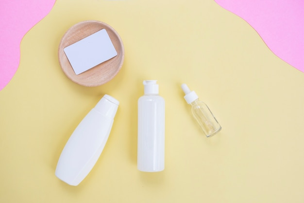 Cosmetic bottle beauty background and business card on yellow and pink paper background. summer skin care concept