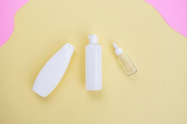 Косметическая бутылка красоты фон на желтом и розовом бумажном фоне. концепция ухода за кожей летом