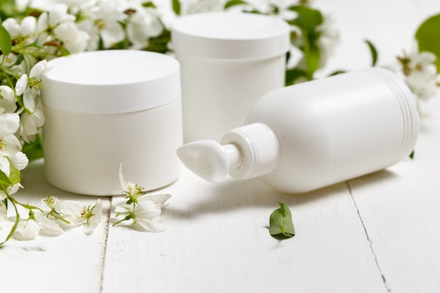 Cosmetic bottle close up with white spring flowers on the white background