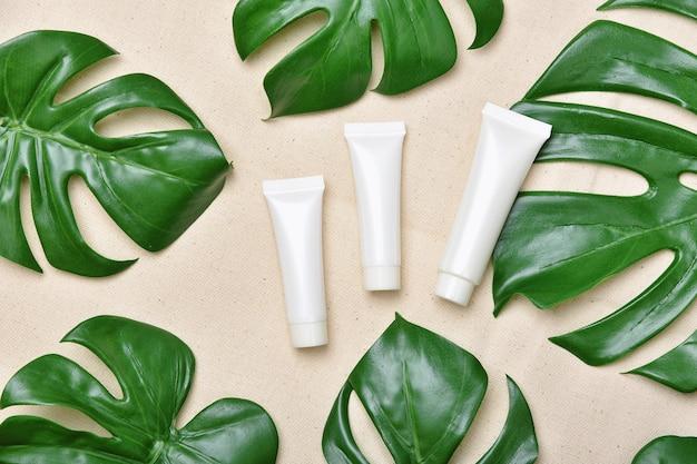 緑のハーブの葉で包装された化粧品のボトル容器、オーガニックブランドのモックアップ用の空白のラベル