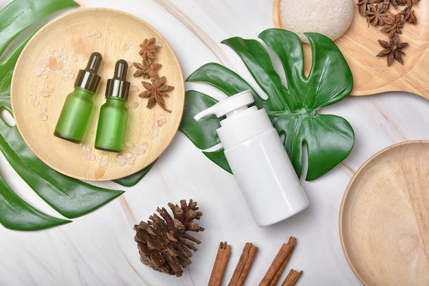 Cosmetic bottle containers packaging with green herbal leaves, blank label for organic branding mock-up