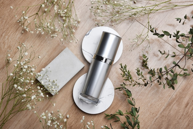 Cosmetic bottle containers packaging with green herbal leaves, blank label for organic branding, natural skincare beauty product concept.