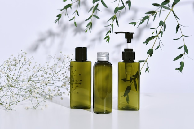 Cosmetic bottle containers packaging with green herbal leaves in shadow and light effect, blank label for organic branding , natural skincare beauty product concept.
