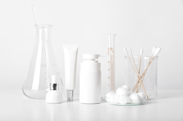 Cosmetic bottle containers and scientific glassware, blank package for branding , pharmaceutical skincare by dermatologist doctor, research and develop beauty product concept.