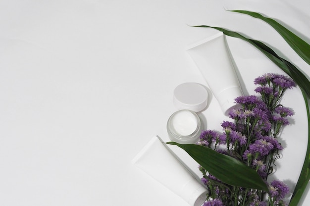 Cosmetic bottle containers white product with flower and leaf.