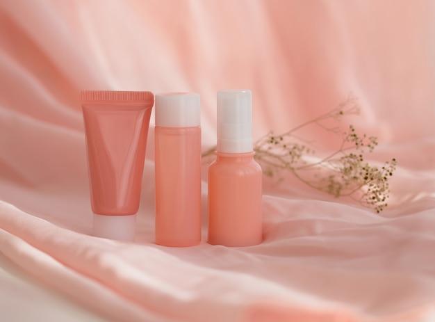 핑크 패브릭 배경에 화장품 병 크림 로션