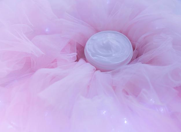 ピンクのチュール生地にクリームローションの化粧品ボトル
