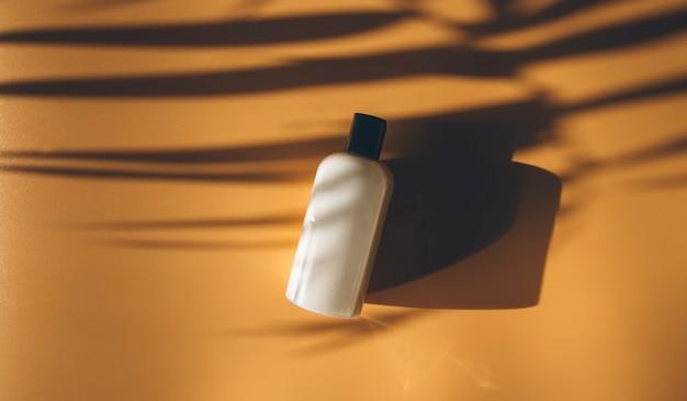 Косметическая бутылка на бежевом фоне