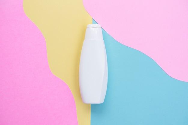 Косметическая бутылка на фоне пастельных тонов. брендовые продукты, красота фон. минималистичный стиль