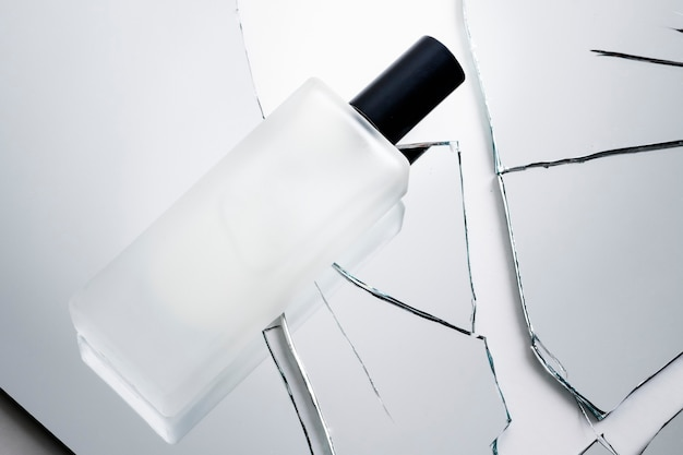 Cosmetic bottle on pieces of broken shattered glass