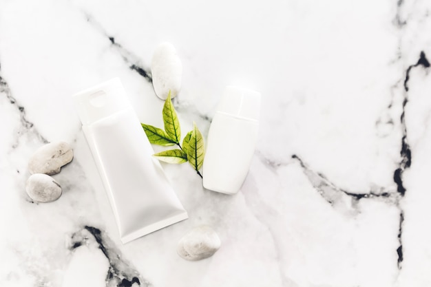 Cosmetic bottle skin care products with spa stones and leaves on white marble background.
