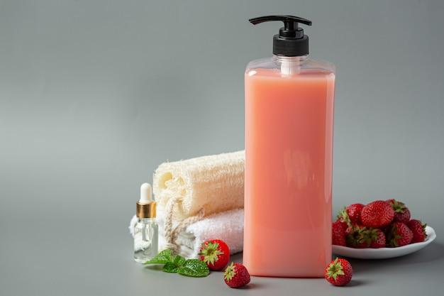 Косметическая бутылка клубничного шампуня на серой поверхности