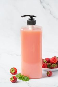 Косметическая бутылка клубничного шампуня на белой поверхности