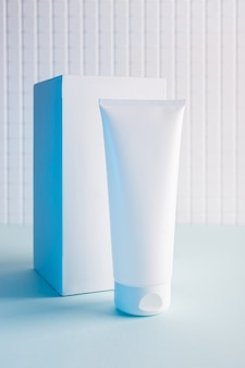 Cosmetic bottle and white cube on a blue background, mock up image