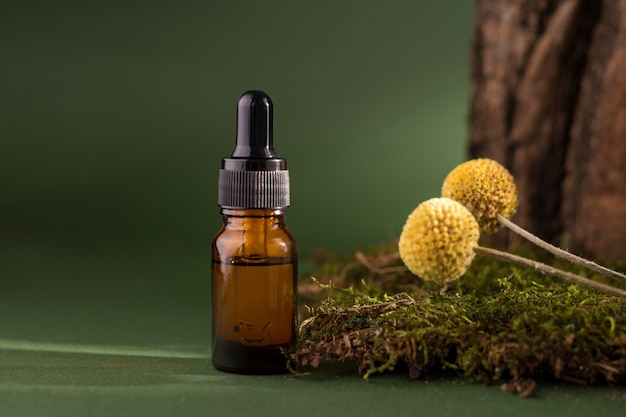 Cosmetic bottle with dropper on a wooden bark, moss decorated with dry craspedia also known as billy balls. pine tree essential oils on a dark green background.