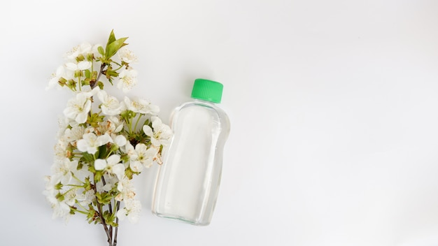 Cosmetic bottle with flowers isolated on white background