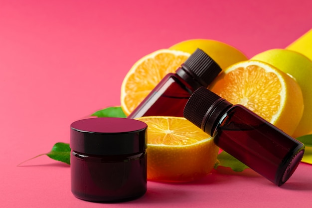 Cosmetic bottle with sliced citrus fruits on bright pink wall